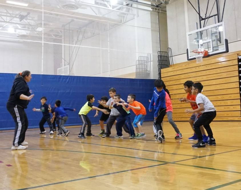 Kids playing basketball during a Leisure Unlimited kid's class.