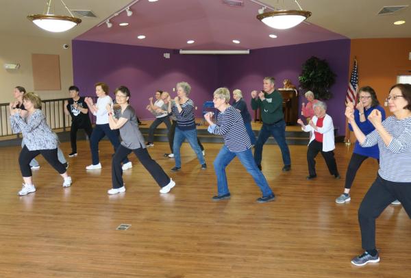 Adults participate in an aerobics class.