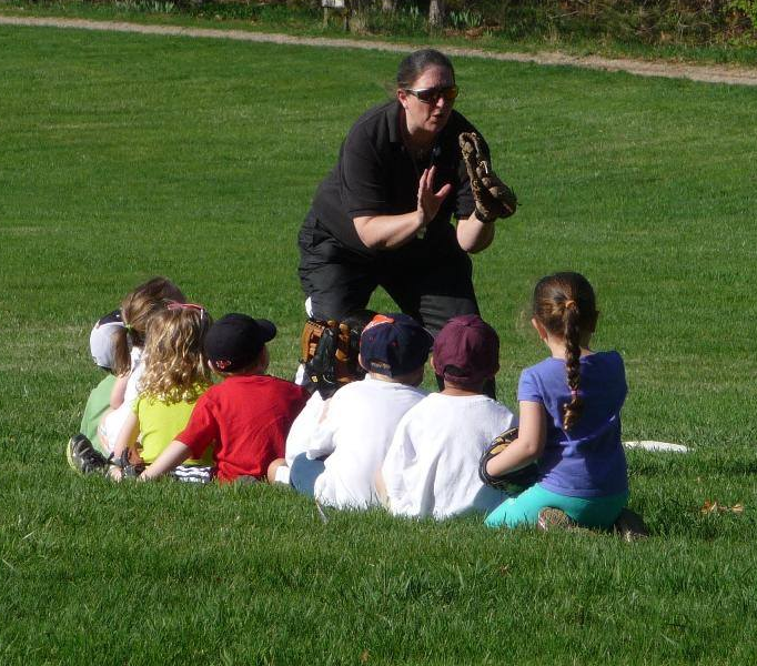 Coach Jo teaches children how to catch a baseball with a glove.