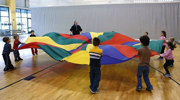 Kids work together to play parachute games.
