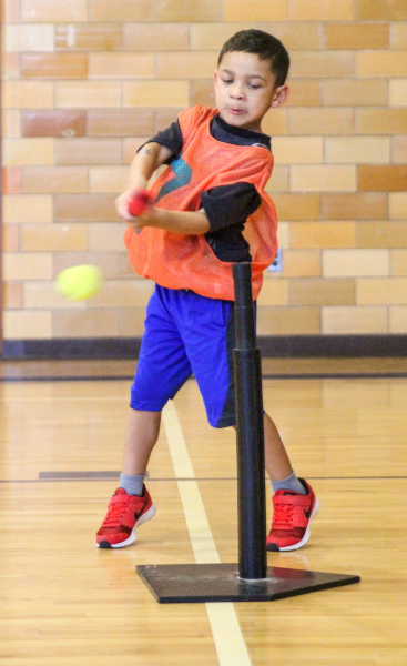 A boy swings a bat at a tee ball in a gumnasium.